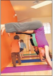 photo courtesy Autumn Oglesby. Easter Bonnifield (front right), Avery Kalapa (middle right) and Heather Lee Farrell (back right) form a handstand tunnel for children to run through as part of a children's yoga practice